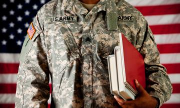 Military student holds books in from of American flag.