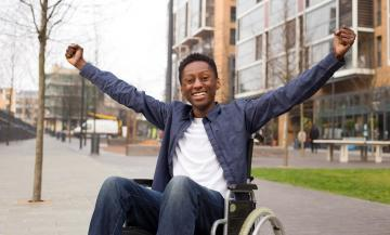 Student in wheelchair celebrates outside university building.